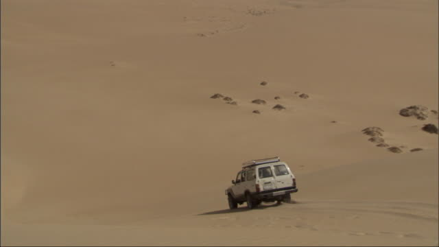 Medium Long Shot, tracking-left - A vehicle drives down a steep sand dune in the Sahara Desert in Egypt