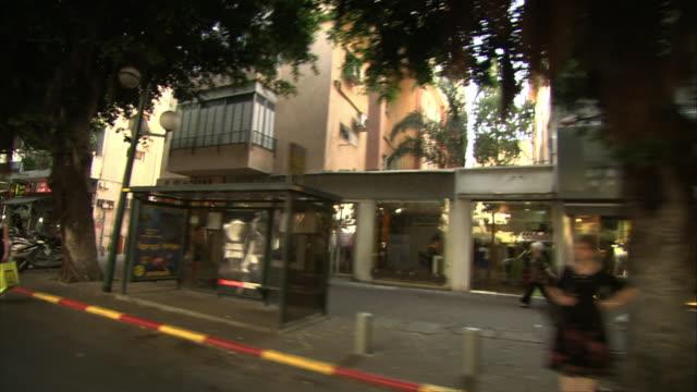 medium long shot tracking-left - shoppers and other pedestrians pass storefronts in downtown tel aviv. / tel aviv, israel - tel aviv stock-videos und b-roll-filmmaterial