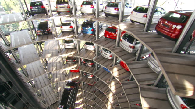 medium long shot_crane - a hydraulic arm lifts a car into position in a tower garage. / wolfsburg, germany - automobile industry video stock e b–roll