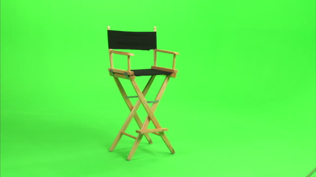 medium long shot_static - a director's chair sits in front of a green screen.   - stol bildbanksvideor och videomaterial från bakom kulisserna