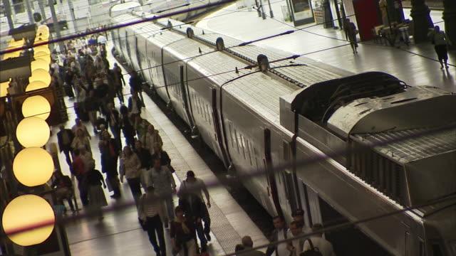 medium long shot_static - travelers walk alongside a train in a station. / paris, france - pedone ruolo dell'uomo video stock e b–roll