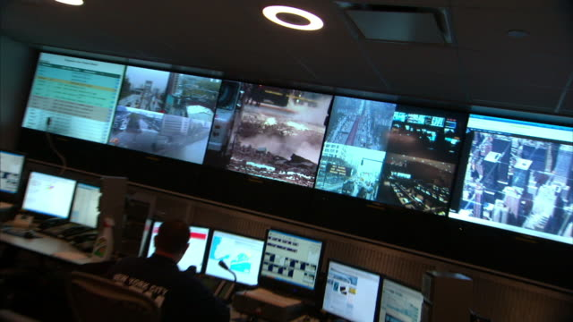 medium long shot_tracking-left zoom-out - situation monitors surround police dispatchers in a new york city police control room. / new york city, new york, usa - kontrollraum stock-videos und b-roll-filmmaterial