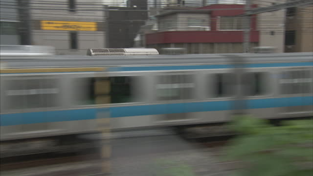 Medium Long Shot_tracking-right - A commuter train speeds past neighborhoods and past a station in Tokyo. / Tokyo, Japan