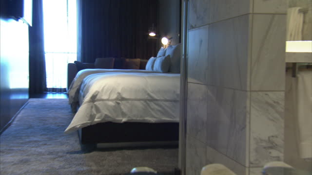 Medium Long Shot_zoom-out - A bedroom reflects in the mirror of a luxurious bathroom. / Las Vegas, Nevada, USA