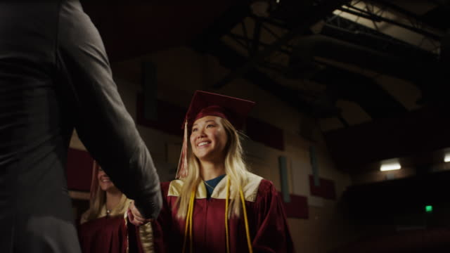 medium low angle panning shot of high school graduate waving at graduation / mapleton, utah, united states - graduation stock videos & royalty-free footage