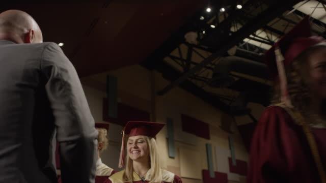 vidéos et rushes de medium low angle panning shot of high school graduates on stage at graduation / mapleton, utah, united states - chapeau