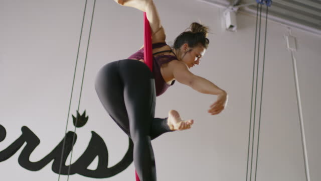 medium low angle panning shot of woman practicing on aerial silks / midvale, utah, united states - legs apart stock videos and b-roll footage