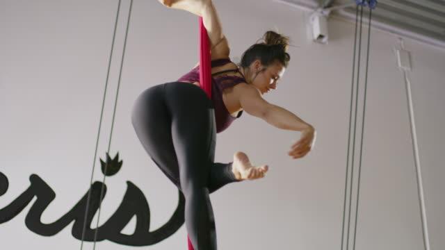 medium low angle panning shot of woman practicing on aerial silks / midvale, utah, united states - legs apart stock videos & royalty-free footage