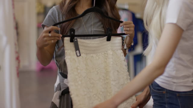 medium low angle panning shot of women examining skirt in clothing store / american fork, utah, united states - skirt stock videos & royalty-free footage