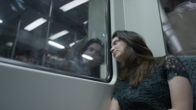 Medium low angle shot of bored woman leaning on window in train / Berlin, Germany