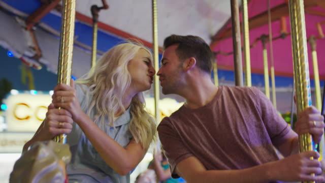 vídeos de stock, filmes e b-roll de medium low angle shot of couple kissing on carousel / pleasant grove, utah, united states - carousel