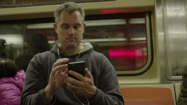 Medium low angle shot of man using cell phone on subway / New York, New York, United States