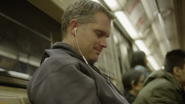 Medium low angle shot of man using cell phone on subway / New York, New York, United States