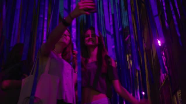 vídeos y material grabado en eventos de stock de medium low angle shot of women posing for cell phone selfie under streamers / plovdiv, bulgaria - sin mangas