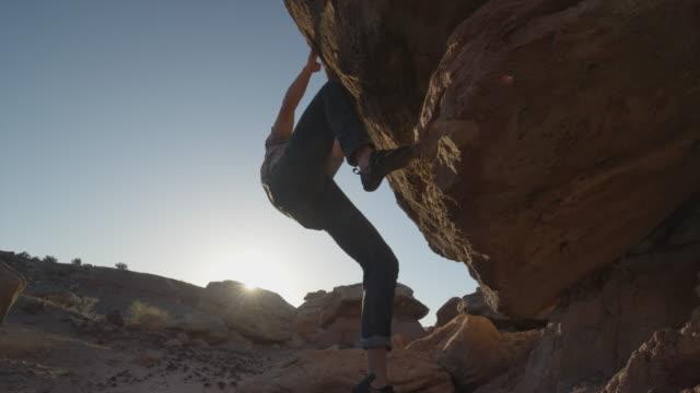 Medium low angle slow motion shot of man climbing rock / Ferron, Utah, United States