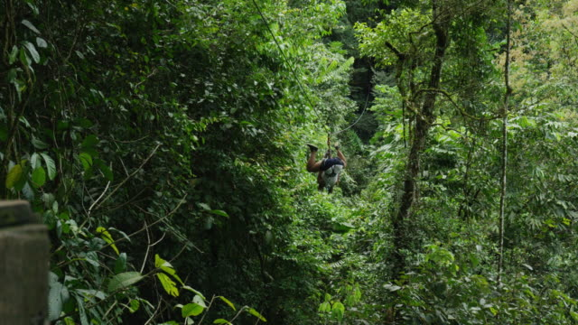 Medium low angle tracking shot of woman ziplining to landing in forest / Quepos, Puntarenas, Costa Rica