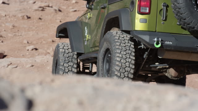 Medium low angle view of car driving on rocks in desert / Moab, Utah, United States