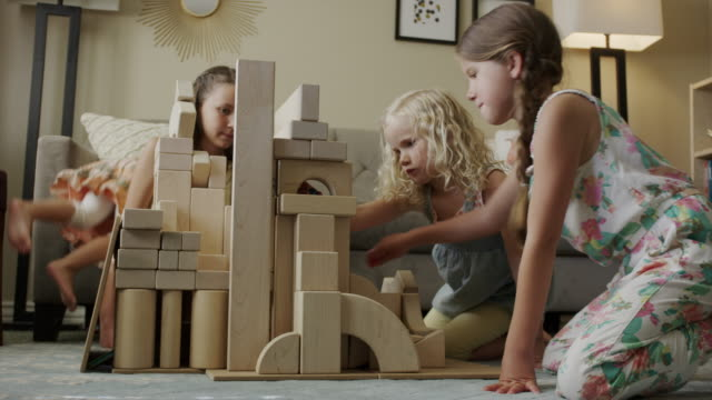 medium low angle view of girls playing on floor with building blocks / orem, utah, united states - orem bildbanksvideor och videomaterial från bakom kulisserna