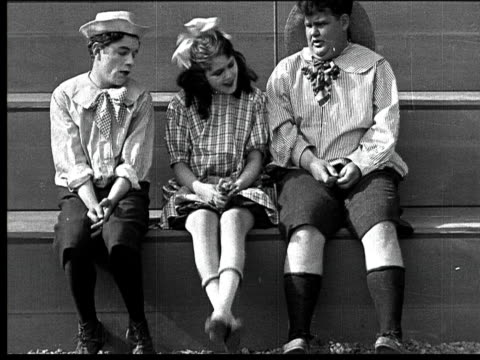 1918 b/w medium man dressed as child scooting along step to where man and woman dressed as children are sitting/ woman giving two lollipops to one boy and two to the other - oliver hardy stock videos & royalty-free footage