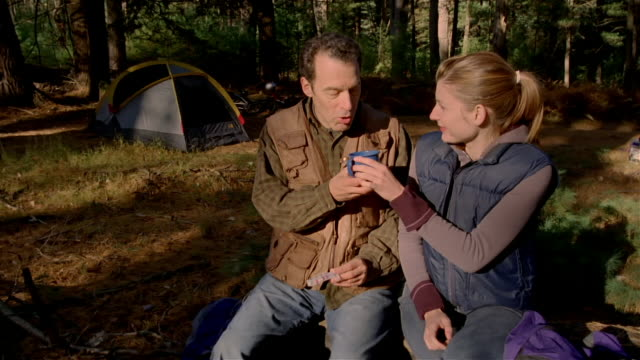 Medium man opening pillbox and swallowing pill / woman handing him mug