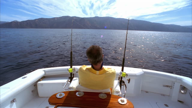 Medium man sitting in fighting chair on yacht as he gets a bite on his fishing line/ men surrounding friend as he struggles with fish on line/ California