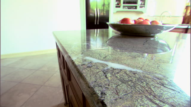 Medium move right across a kitchen with a granite countertop.