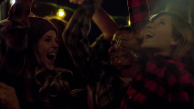 vídeos de stock e filmes b-roll de medium pan across group young adults dancing to dj tilting up to hands (slo-mo) - luz estroboscópica