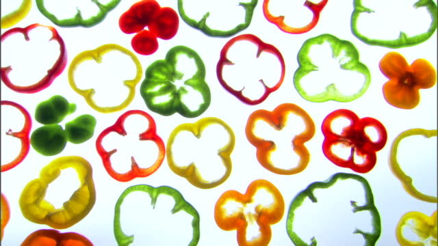 vídeos de stock, filmes e b-roll de medium pan left of sliced colorful bell peppers on a backlit surface. - medium group of objects