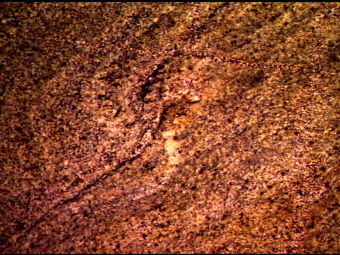 medium pan right across red-brown toned granite stone. - igneous stock videos & royalty-free footage