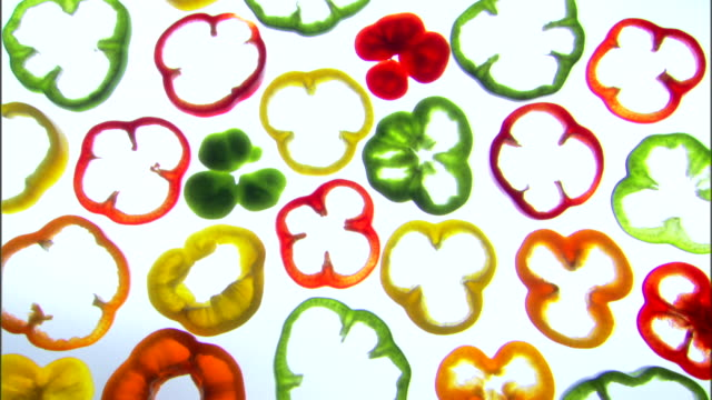 vídeos de stock, filmes e b-roll de medium pan right of sliced colorful bell peppers on a backlit surface. - medium group of objects