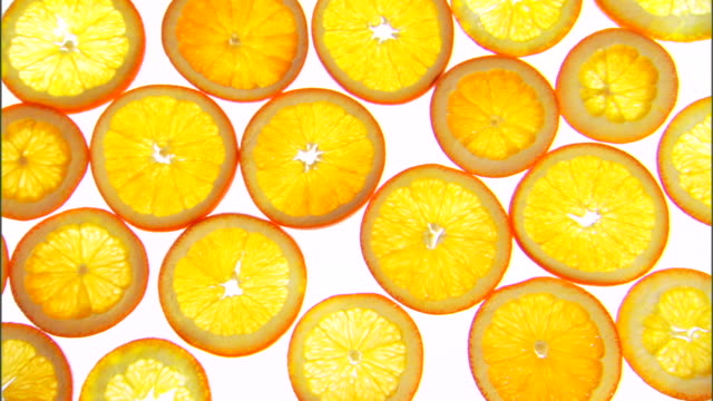 vídeos de stock, filmes e b-roll de medium pan right over slices of oranges lying on a backlit surface. - medium group of objects