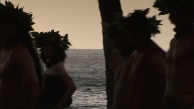medium pan-left - hula dancers wearing haku made of ti leaves on their heads perform at sunset. / kona, hawaii, usa - hawaiian culture stock videos & royalty-free footage
