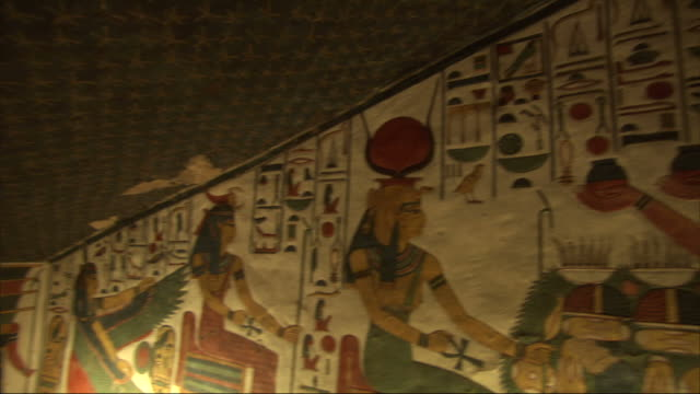 Medium, pan-left push-in  - Murals depict ancient Egyptian life in a low-ceiling room