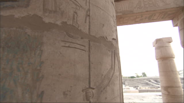 Medium, pan-left push-in tracking-right - Columns at an ancient Egyptian ruin site contain drawings and hieroglyphics