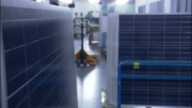 Medium pan,left rack,focus zoom,in , Factory workers assemble solar panel parts. / California