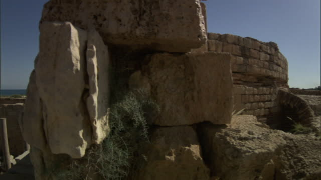 medium pan-left - stacked blocks face a roman arena and the other ruins of leptis magna. / khoms, libya - stein baumaterial stock-videos und b-roll-filmmaterial
