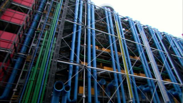 Medium pan-left tilt-down - Colorful pipes cover the exterior of the Pompidou Centre in Paris. / Paris, France