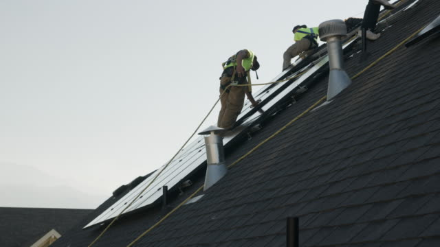 medium panning low angle shot of worker carrying solar panel on roof / mapleton, utah, united states - installing stock videos and b-roll footage