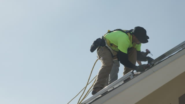 medium panning low angle shot of workers installing rails on roof / mapleton, utah, united states - imbracatura di sicurezza video stock e b–roll