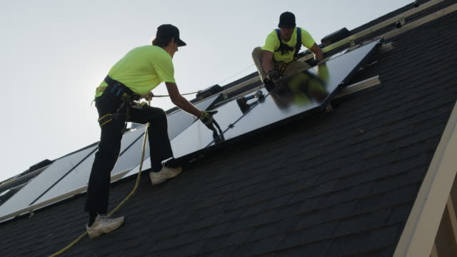 medium panning low angle shot of workers installing solar panel on roof / mapleton, utah, united states - imbracatura di sicurezza video stock e b–roll