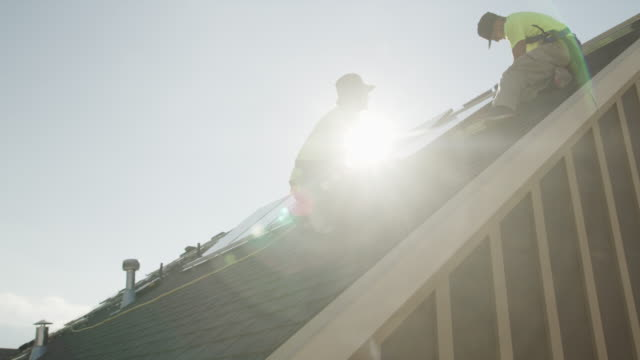 medium panning low angle shot of workers installing solar panel on roof / mapleton, utah, united states - industriegerät stock-videos und b-roll-filmmaterial