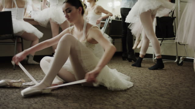Medium panning shot of ballerina sitting on floor putting on ballet shoe / Salt Lake City, Utah, United States