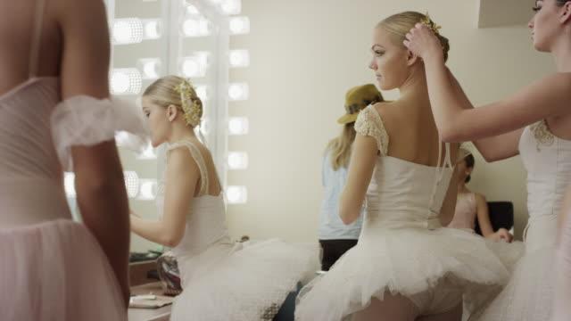Medium panning shot of ballerinas preparing in busy dressing room / Salt Lake City, Utah, United States