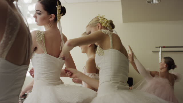 Medium panning shot of ballerinas preparing in busy dressing room / Salt Lake City, Utah, United States