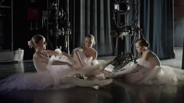 Medium panning shot of ballerinas stretching backstage / Salt Lake City, Utah, United States
