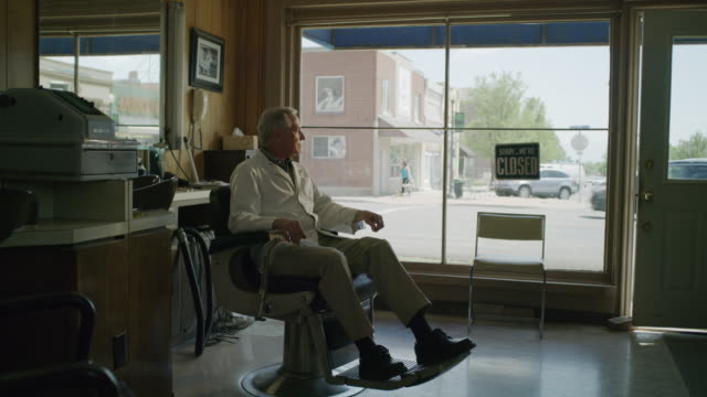 Medium panning shot of barber waiting in chair / Pleasant Grove, Utah, United States