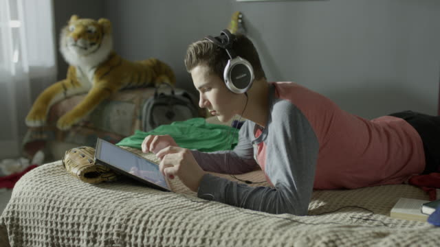 Medium panning shot of boy using digital tablet and headphones in bed / Cedar Hills, Utah, United States