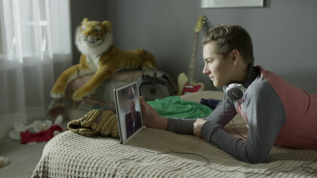 Medium panning shot of boy video chatting with father on digital tablet in bed / Cedar Hills, Utah, United States