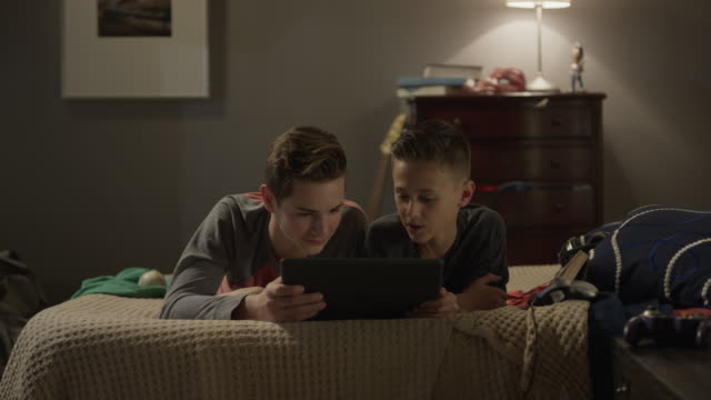 medium panning shot of boys watching digital tablet on bed / cedar hills, utah, united states - sibling stock videos & royalty-free footage