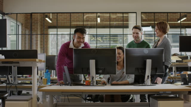 vidéos et rushes de medium panning shot of business people working together in office / lehi, utah, united states - droit